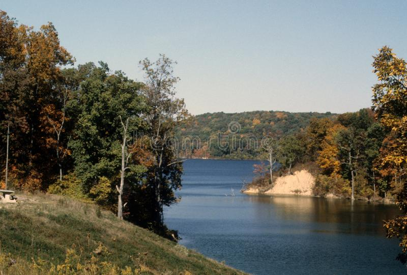 Midwestern autumn scene with colorful trees and a lake. Colorful fall scene with trees, sunny blue sky, a lake , Brookville Lake in southeastern Indiana royalty free stock photo