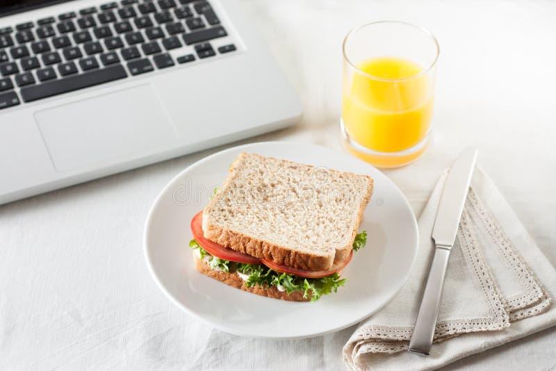 Mieć kanapkę i sok pomarańczowego jako przekąska podczas gdy pracujący zdjęcie stock
