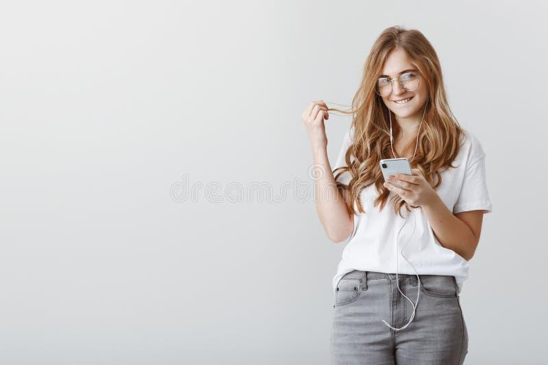 Mieć paskudnych pomysły w umysle Portret piękny powabny blondynka uczeń w szkłach, trzyma smartphone, zjadliwa warga i zdjęcia stock