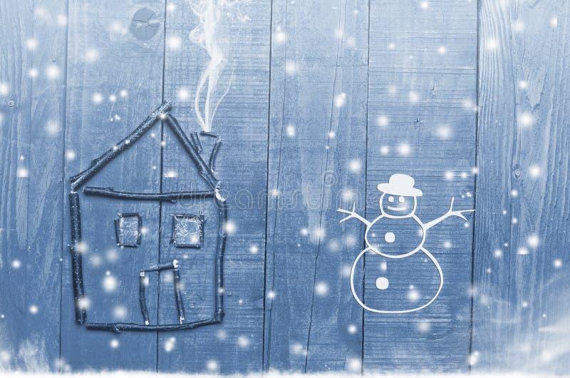 Mieści ustawionego od gałązek na drewnianej zimy śnieżnym błękitnym tle Bałwan zdjęcia royalty free