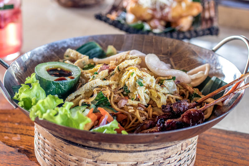 Mie goreng, mi goreng, indonesian fried noodles with beautiful decoration on a wooden table. Bali island. royalty free stock photo