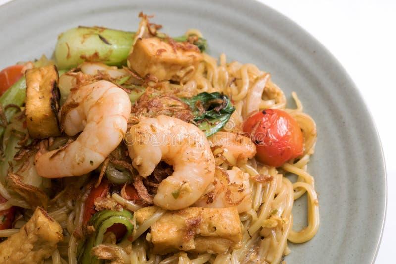 Mie goreng, stekt berömd indonesisk kryddig maträtt för gul för nudelräka havs- för grönsak för tomat för ägg för vitlök för scha arkivfoto