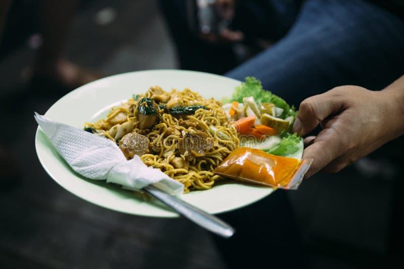 Mie Goreng tjänade som med chilisås och bestick från gatanattmarknad i Jakarta, Indonesien royaltyfri bild