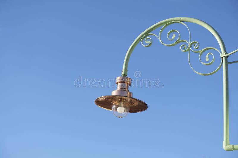Miedziana lekka latarniowa lampa i wielka szklana żarówka przeciw niebieskie niebo wiktoriański rocznikowi projektujemy obrazy royalty free