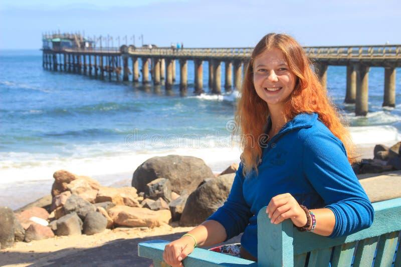 Miedzianowłosa szczęśliwa biała Kaukaska dziewczyna siedzi na ławce na brzeg Atlantycki ocean w Swakopmund Namibia i śmia się zdjęcia stock