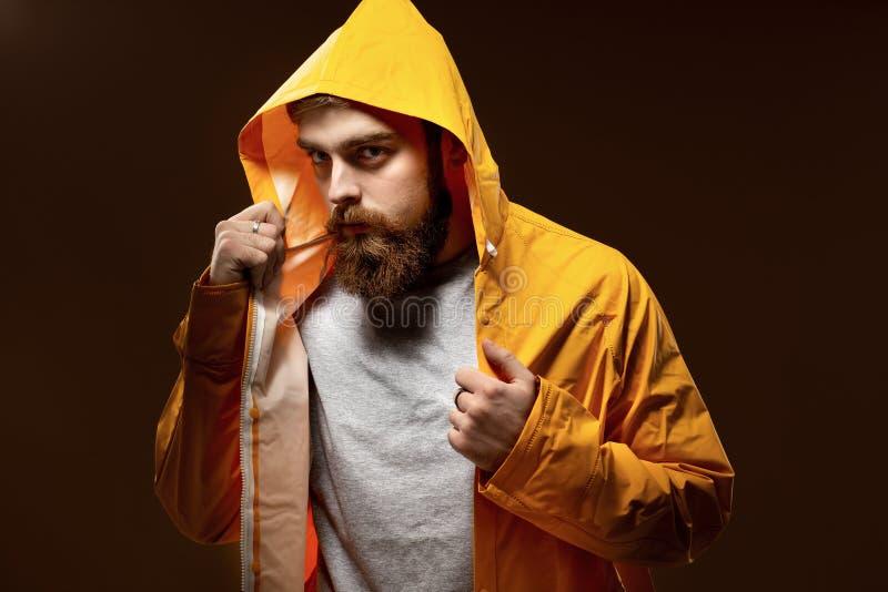 Miedzianowłosy facet z brodą ubierającymi w wąsy i szarej koszulce żółtej kurtce z kapiszonem i pozuje na brązie fotografia royalty free