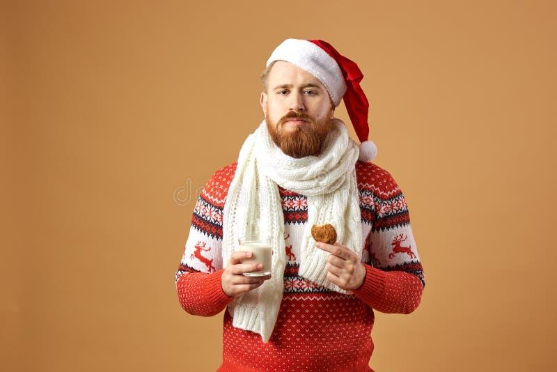 Miedzianowłosy mężczyzna z brodą ubierał w pulowerze z rogaczami, białym trykotowym szaliku i kapeluszu Święty Mikołaj czerwonym  fotografia stock