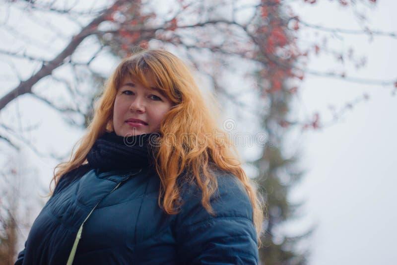 Miedzianowłosa dziewczyna w zielonej kurtce na ulicie fotografia stock