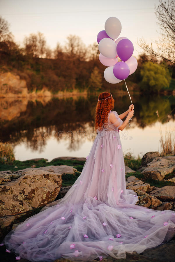 Miedzianowłosa kobieta z balonami w ona w czarodziejskiej purpurze i ręka ubiera przy zmierzchem zdjęcia stock