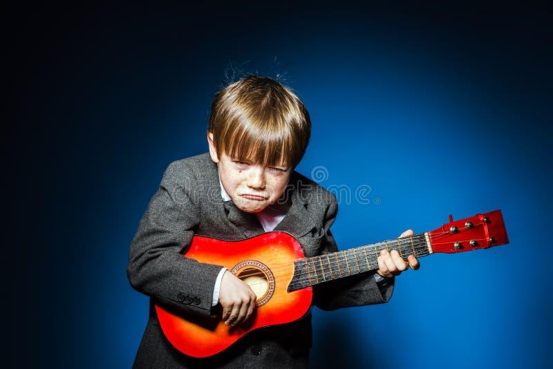 Miedzianowłosa preschooler chłopiec z ukalele, muzyczny pojęcie fotografia stock