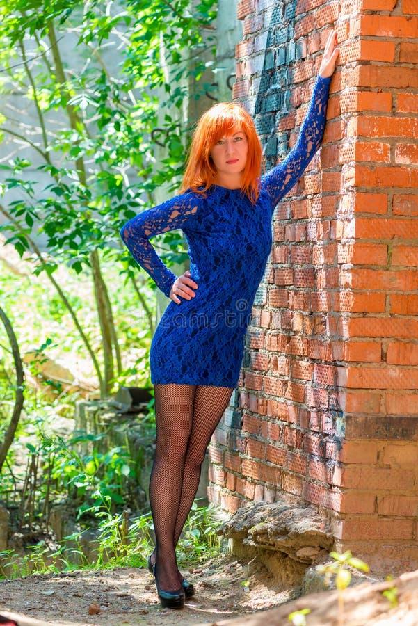 Miedzianowłosi dziewczyna stojaki blisko ściana z cegieł zdjęcie royalty free
