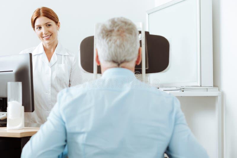Miedzianowłosy oftalmolog ono uśmiecha się podczas gdy patrzejący pacjenta zdjęcie royalty free