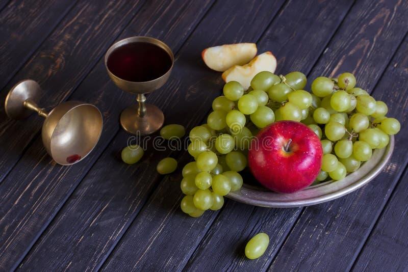 Miedziany szkło z win jabłkami na ciemnym drewnianym tle i winogronami obrazy stock