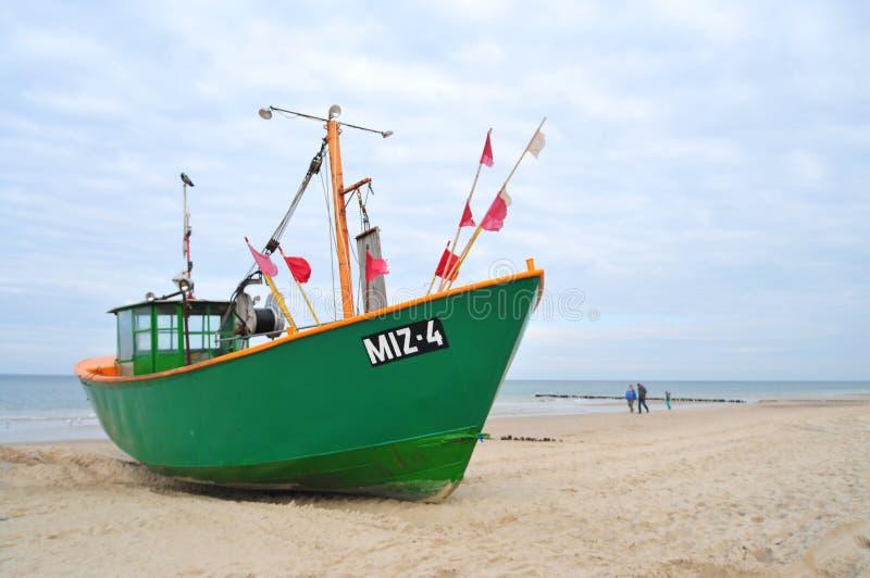 Miedzyzdroje, Poland, November 2018: Green fishing boat on the sandy beach on the Baltic Sea royalty free stock photo