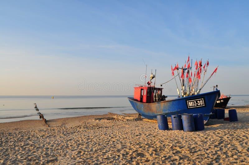 Miedzyzdroje Polen, November 2018: Grön fiskebåt på den sandiga stranden på Östersjön royaltyfri foto