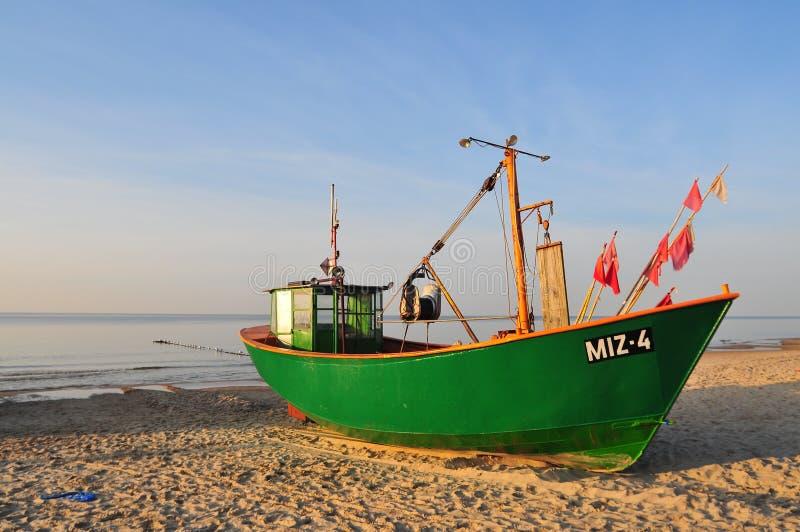 Miedzyzdroje Polen, November 2018: Grön fiskebåt på den sandiga stranden på Östersjön arkivbilder