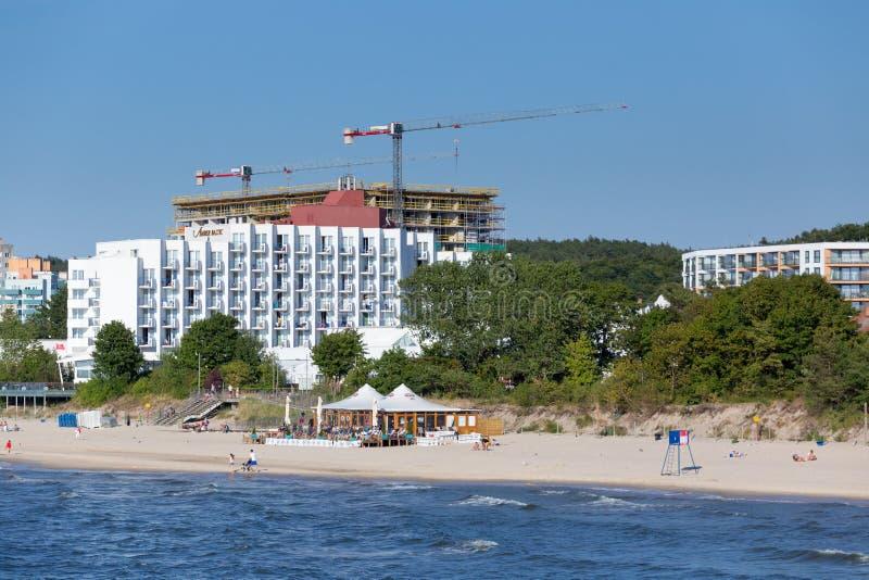 MIEDZYZDROJE, POLONIA - 28 DE JUNIO DE 2018 Nuevo edificio del hotel con las grúas cerca de Amber Baltic Hotel y de la playa en M fotografía de archivo libre de regalías