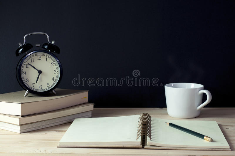 Miejsca pracy notatnik, ołówek, książki, filiżanka kawy i zegar, obraz stock
