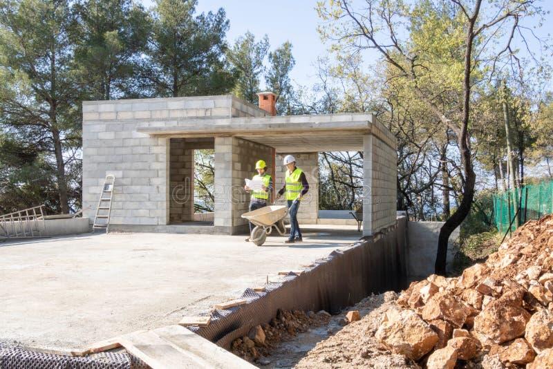Miejsce kierownik daje instrukcjom kamieniarz na budowie dom w budowie zdjęcie stock