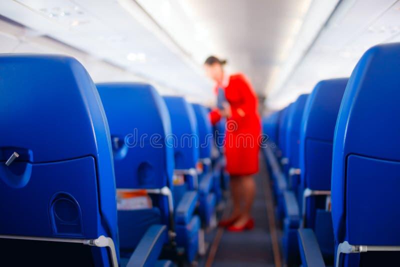 Miejsce pasażera, wnętrze samolot z pasażerami siedzi na siedzeniach i stewardesa chodzi nawę w tle, stewardesa s obrazy stock