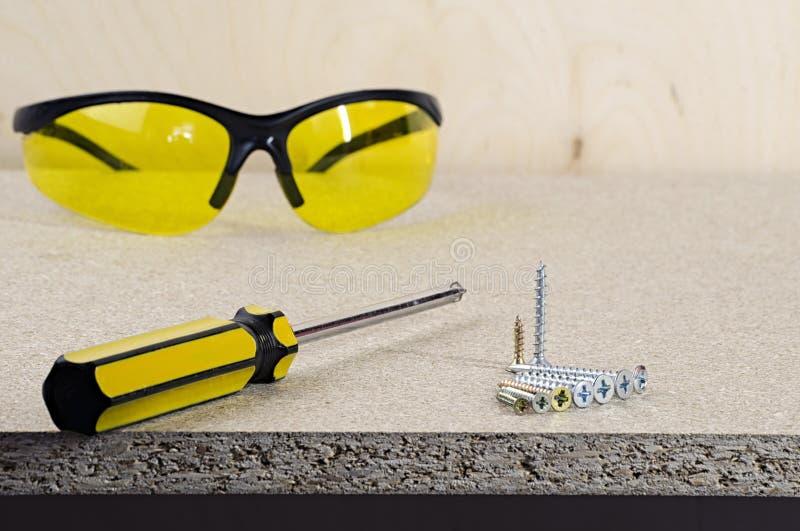 Miejsce pracy, żółty śrubokręt i szkła na drewnianym stole, fotografia stock