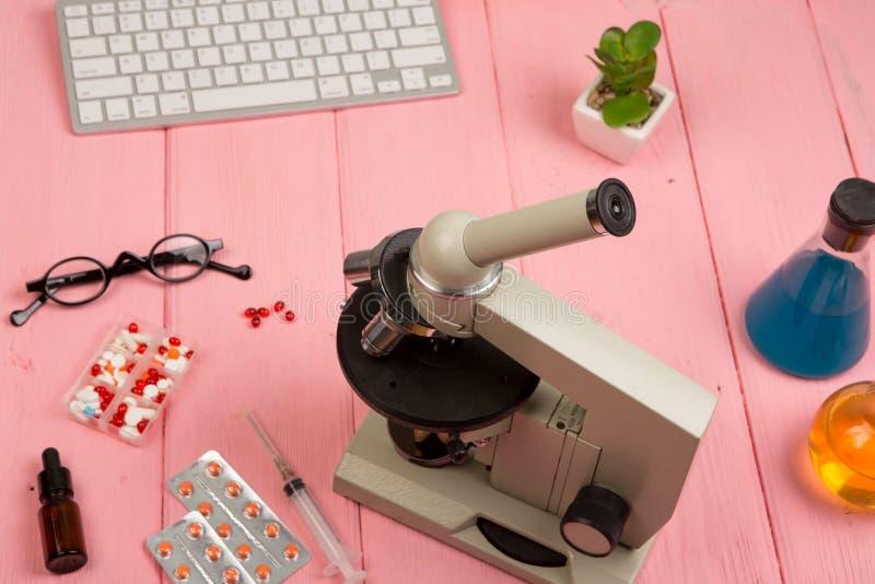 Miejsce pracy naukowiec, lekarka/- mikroskop, pigułki, strzykawka, eyeglasses, chemiczne kolby z cieczem na różowym drewnianym st obrazy stock