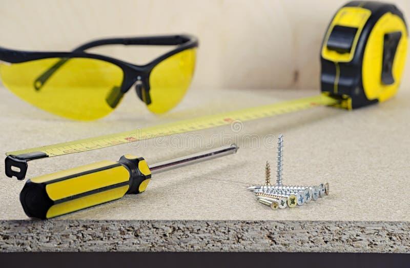 Miejsce pracy, taśmy miara, żółty śrubokręt, szkła i śruby na drewnianym stole, zdjęcie royalty free