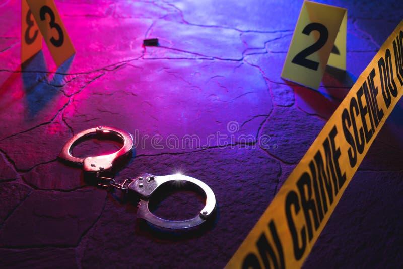 Miejsce przestępstwa kajdanki na podłodze przy nocą zdjęcia stock