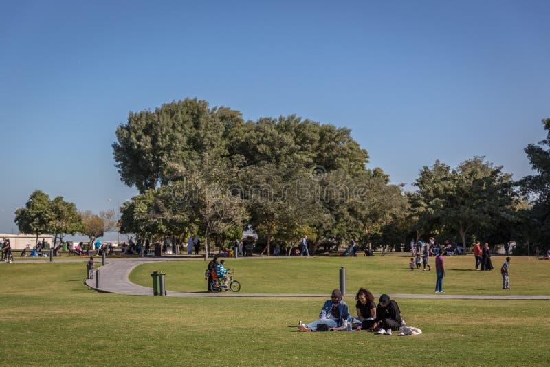 Miejscowy i turyści cieszy się otwartego parka z zielonym polem w łagodnej pogodzie wi drzewa i trawy Doha, Katar, Jan - 9th 2018 zdjęcia stock
