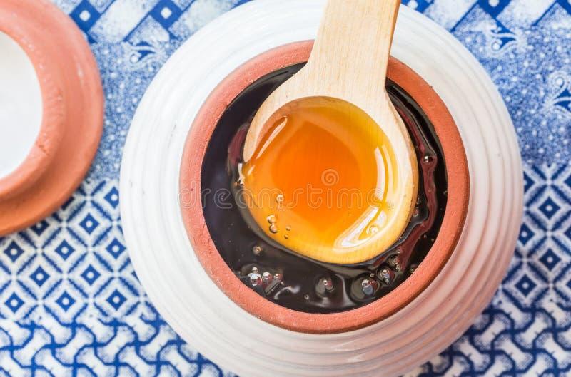 Miel africain cru dans un pot de miel avec la cuillère en bois sur le tissu bleu ethnique photo libre de droits