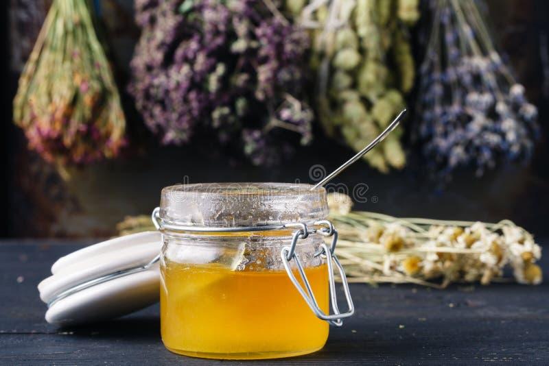 Miel con té en backgound rústico de la tabla con las hierbas imagenes de archivo