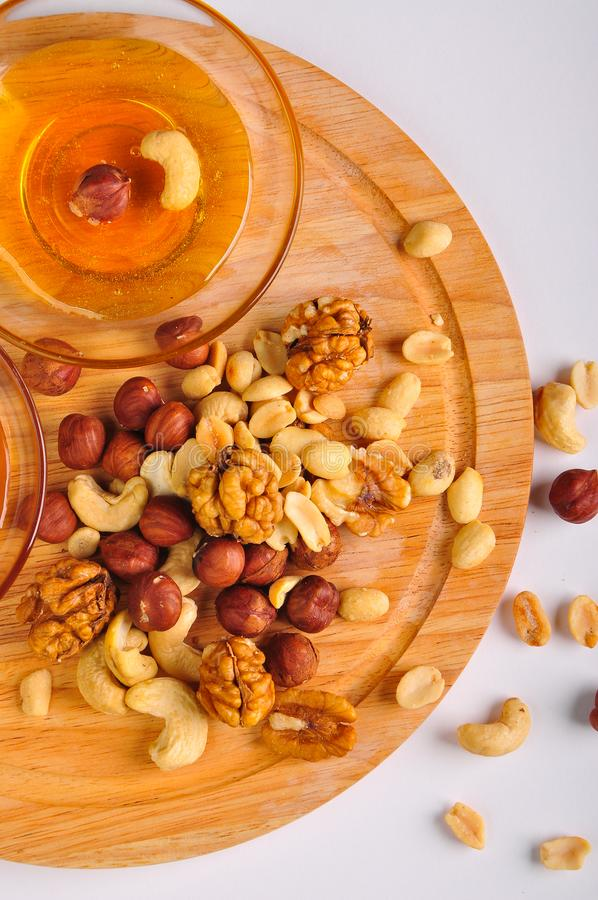 Miel con una mezcla de nueces en un tablero de madera fotos de archivo