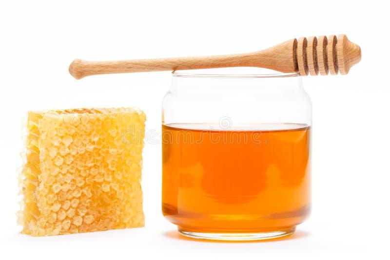Miel dans le pot avec le plongeur et le nid d'abeilles sur le fond d'isolement images stock