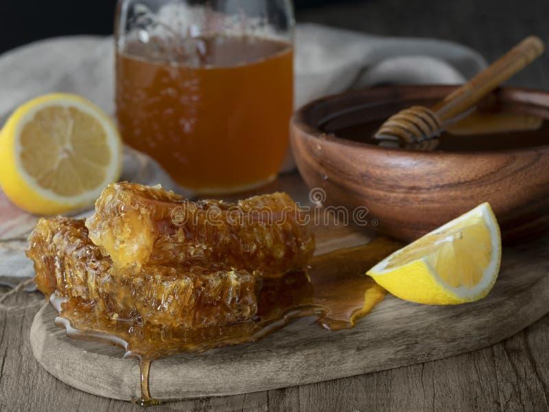 Miel dans le pot avec le nid d'abeilles et le drizzler en bois photographie stock