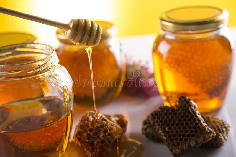 Miel dans le pot avec le plongeur de miel sur le fond en bois images stock