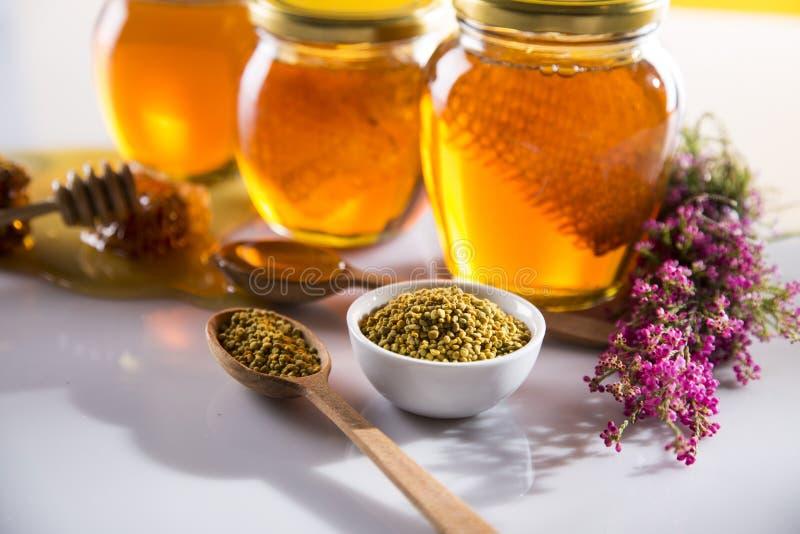 Miel dans le pot avec le plongeur de miel sur le fond en bois photographie stock