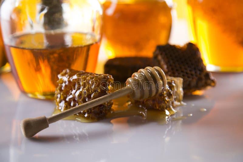 Miel dans le pot avec le plongeur de miel sur le fond en bois photo stock