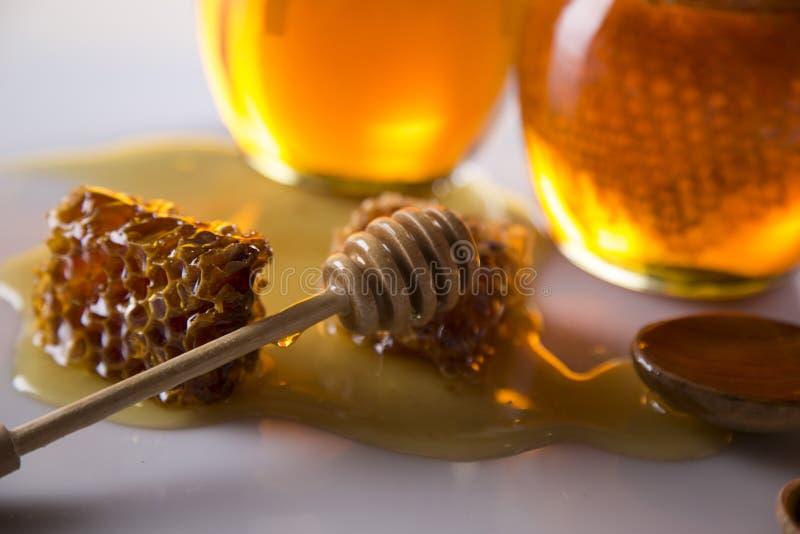 Miel dans le pot avec le plongeur de miel sur le fond en bois image libre de droits