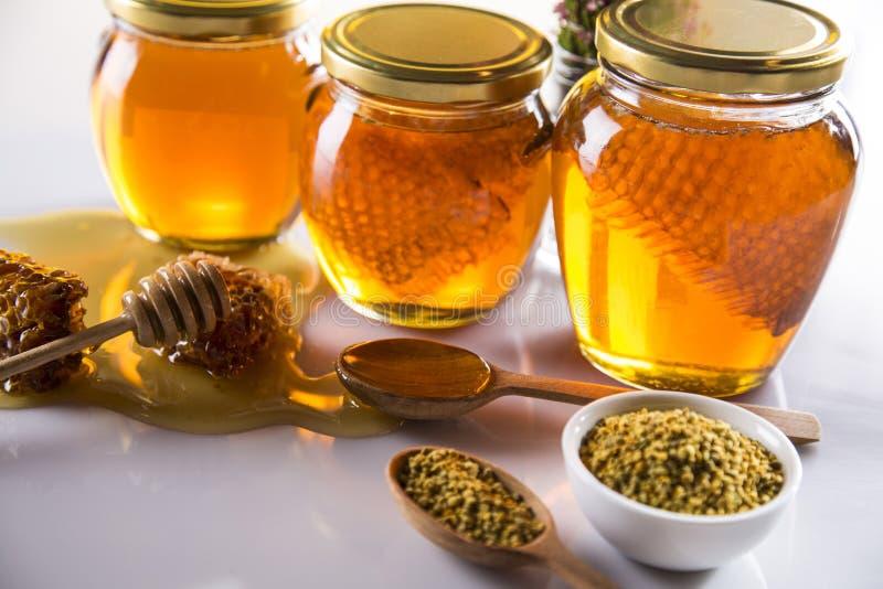 Miel dans le pot avec le plongeur de miel sur le fond en bois image stock