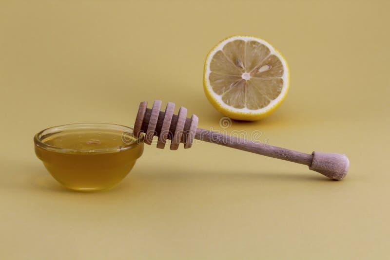 Miel dans un bol en verre avec une cuillère et un citron en bois photo libre de droits