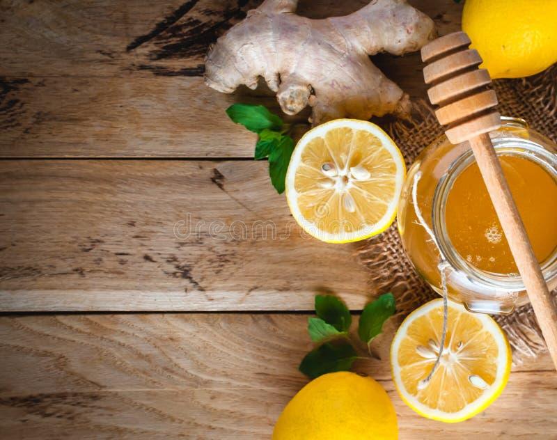 Miel dans un pot avec les citrons, le gingembre et la menthe frais sur le fond en bois, vue supérieure, l'espace de copie photographie stock libre de droits