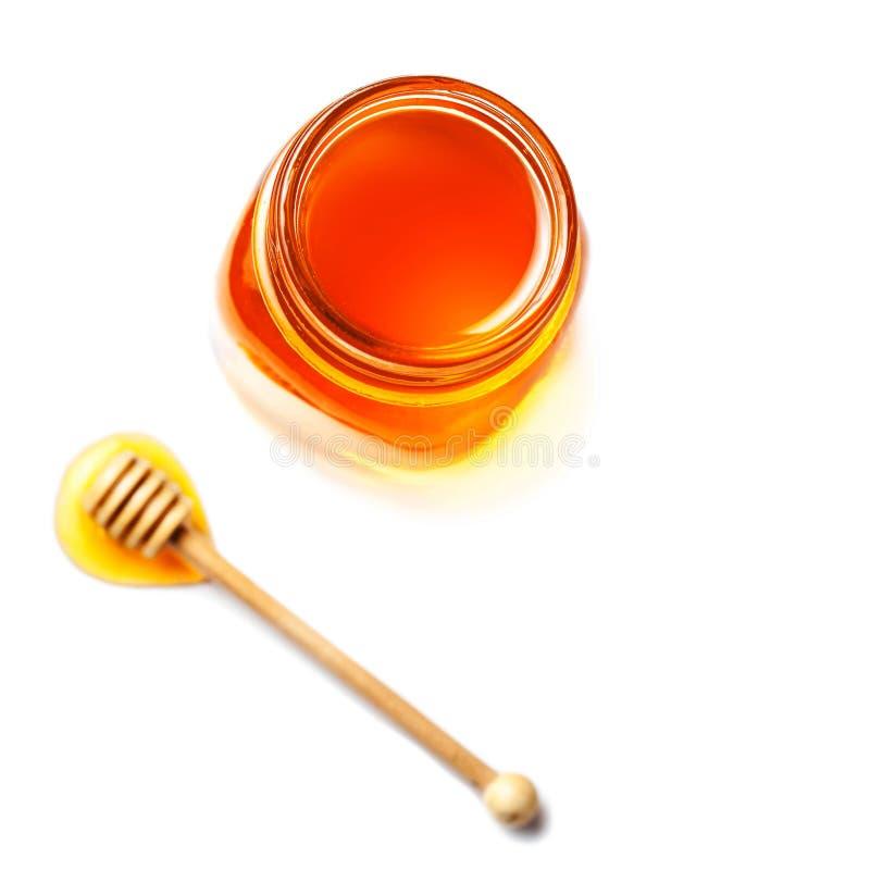 Miel dans un pot en verre avec le plongeur de miel d'isolement sur le backgro blanc image stock