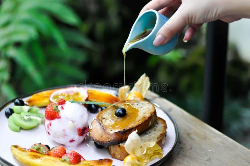 Miel de colada al helado de la baya con la fruta y la tostada foto de archivo libre de regalías