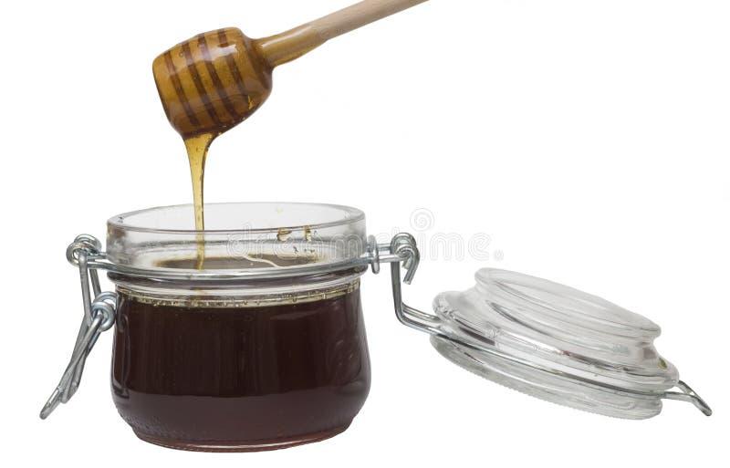 Miel de colada en el pote de cristal en blanco foto de archivo