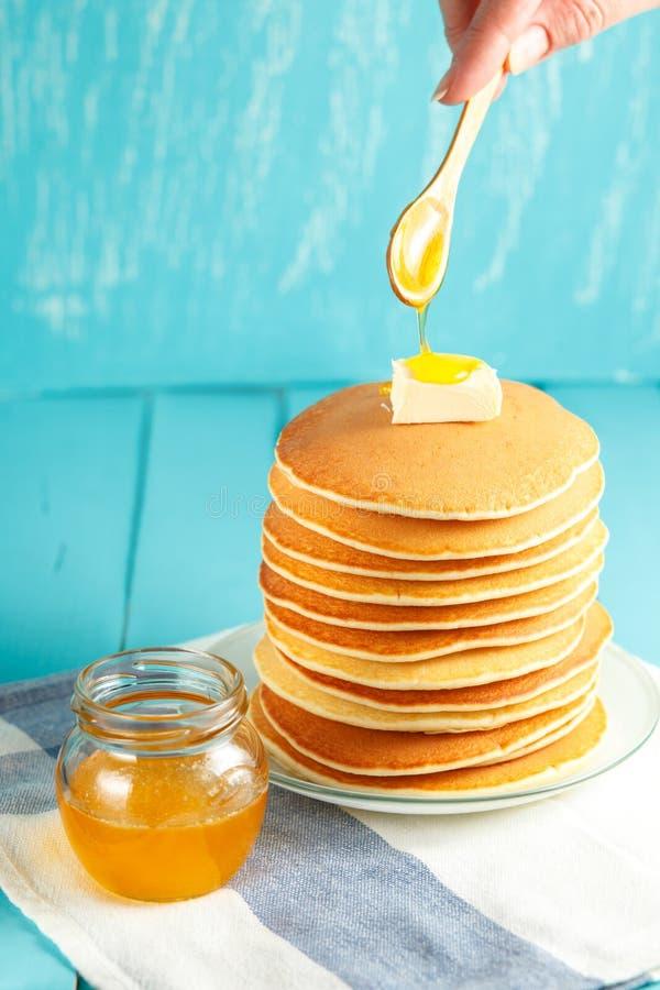 Miel de colada de la mujer sobre la pila de crepes con mantequilla en el top fotografía de archivo