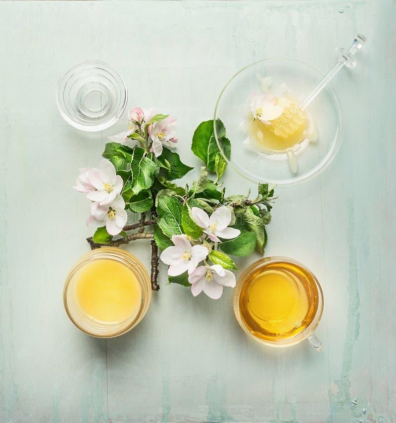 Miel de récolte de ressort dans le pot en verre avec le plongeur, la fleur fraîche et la tasse de thé photographie stock