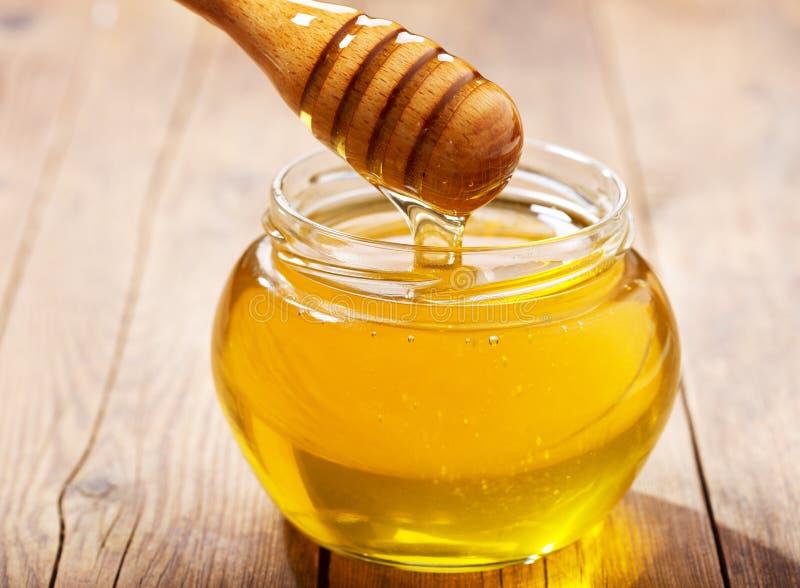 Miel de versement dans le pot photographie stock