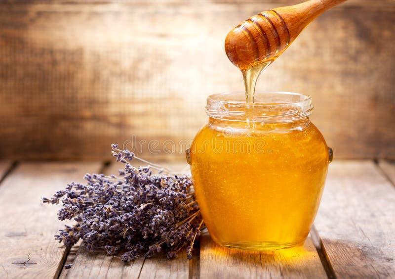 Miel de versement dans le pot de miel de lavande photos libres de droits