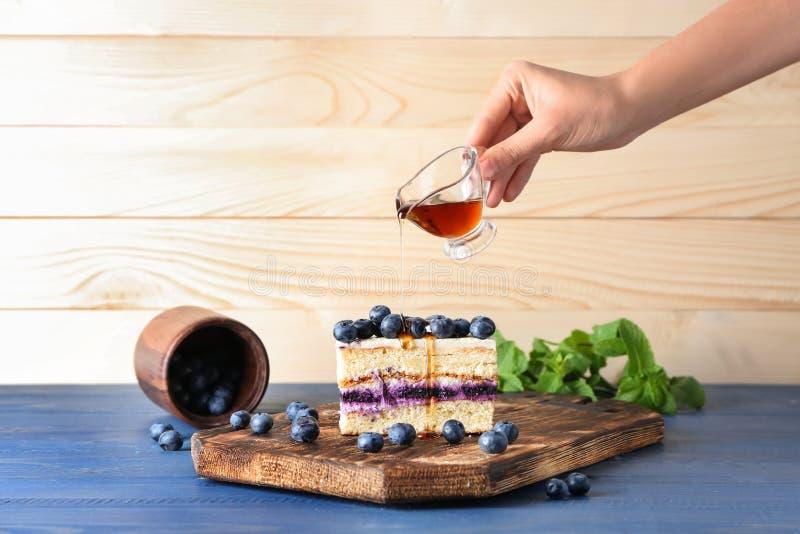 Miel de versement de femme sur le morceau de gâteau délicieux de myrtille sur la table en bois images stock