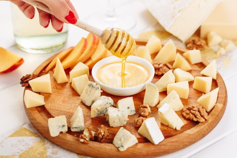 Miel de versement de main de femme au gourmet de panneau de fromage images stock